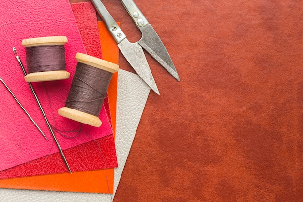 Top view of leather with thread and scissors Free Photo