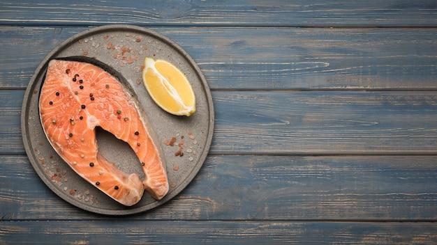 Вид сверху лимон и стейк из лосося на подносе с копией пространства Бесплатные Фотографии
