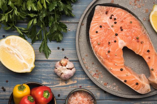 Вид сверху лимон и стейк из лосося на подносе с ингредиентами Бесплатные Фотографии