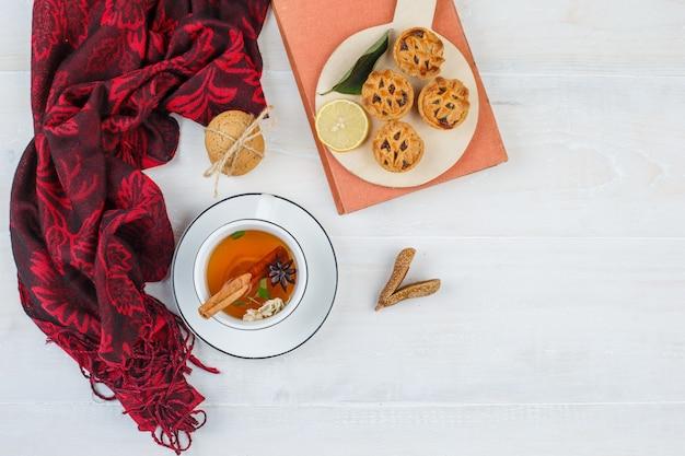 トップビューレモン、赤いスカーフ、白いクッキー、シナモンと白い表面の本とプレートのチョコレートチップクッキー 無料写真