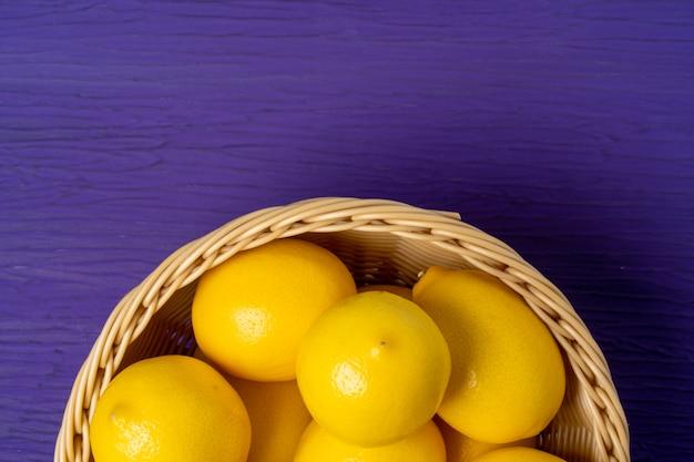 Top view of lemon on purple wooden background Premium Photo