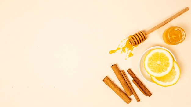 Top view of lemon slice; cinnamon and honey over beige surface Free Photo