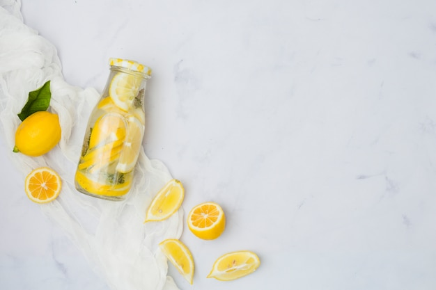 Top view lemonade bottle with lemons Free Photo