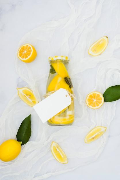 Top view lemonade bottle with lemons Free Photo
