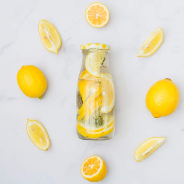Top view lemonade surrounded by lemons Free Photo
