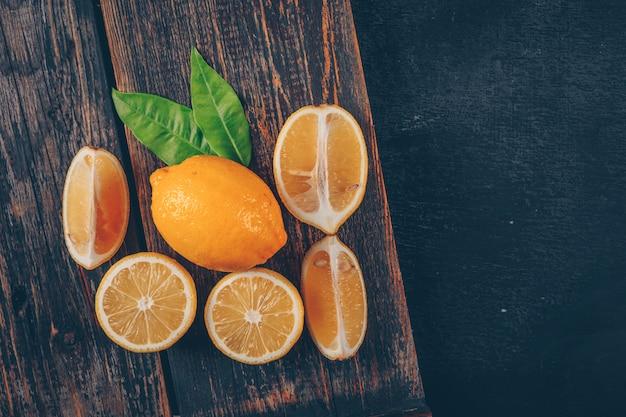 葉と木製のトレイと黒のテクスチャ背景のスライスとレモンの平面図です。横型 無料写真