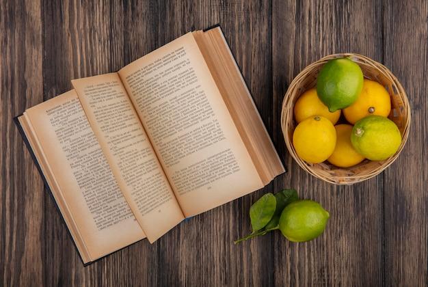 Лимоны с лаймами в корзине с открытой книгой на деревянном фоне, вид сверху Бесплатные Фотографии