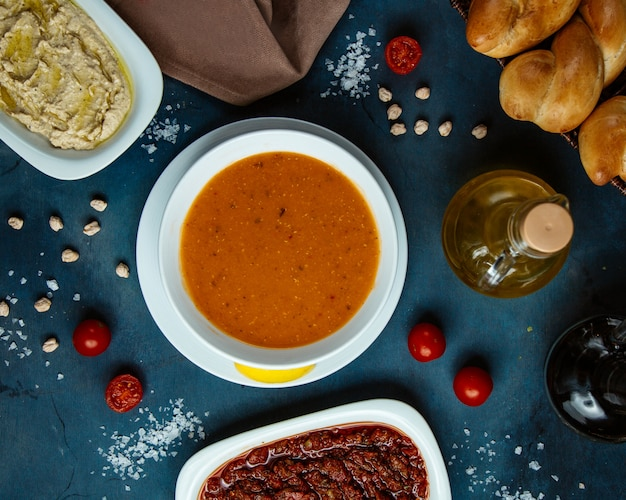 Top view of lentil soup and side dishes and bread Free Photo
