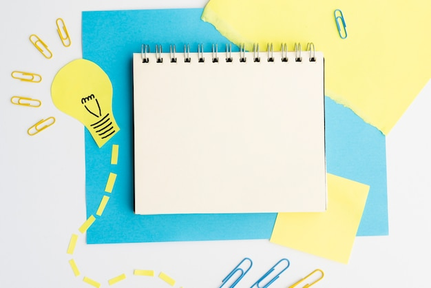 Top view of light bulb cutout and paperclip with blank spiral diary Free Photo