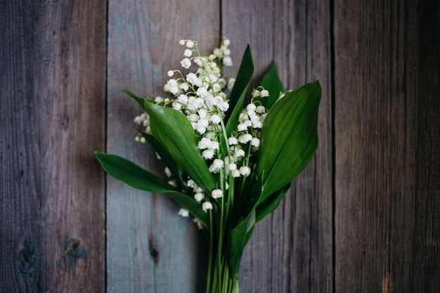 Top view lily of the valley on old wooden background Premium Photo