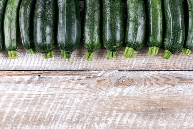 トップビューは、明るい木製のテーブルに新鮮なズッキーニが並んでいます。 無料写真