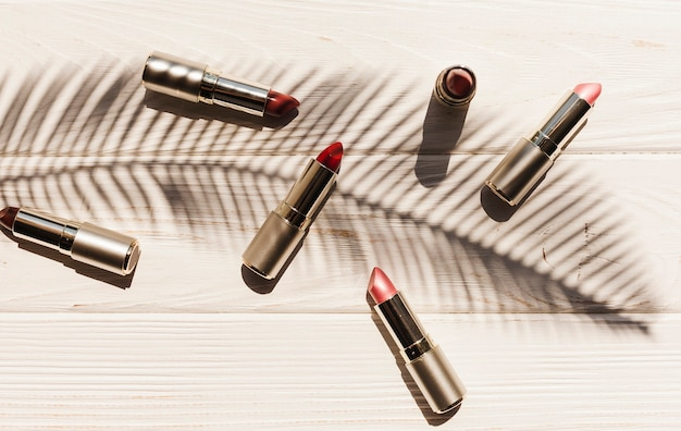 Top view lipsticks with palm branch shadow Free Photo