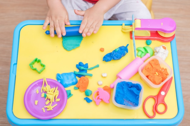 Top view of little asian 2 years old toddler baby boy child having fun playing colorful modeling clay / play dought, cooking toys at play school, educational toys creative play for toddlers concept Premium Photo