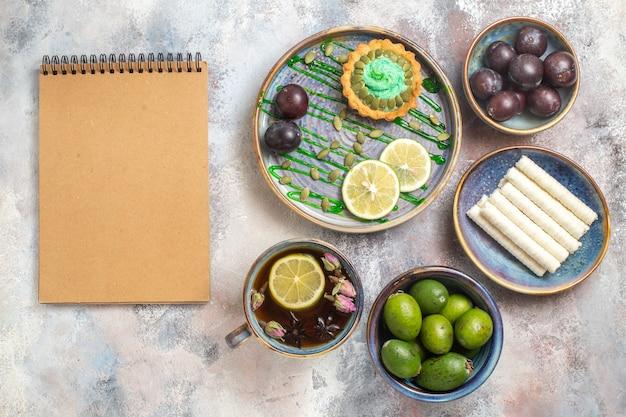 果物とお茶とトップビューの小さなケーキ 無料写真