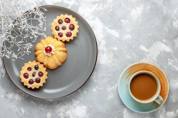 ライトデスクケーキビスケットコーヒーシュガースウィートにミルクコーヒーと灰色のプレート内の小さなケーキの上面図 無料写真
