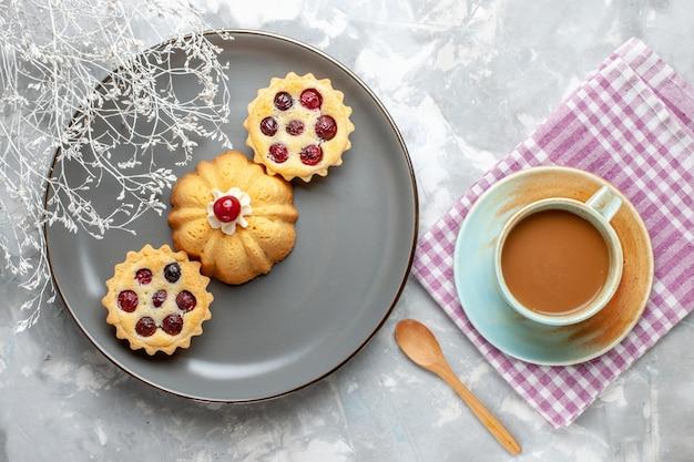 ライトデスクケーキビスケットコーヒースウィートにミルクコーヒーと灰色のプレート内の小さなケーキの上面図 無料写真