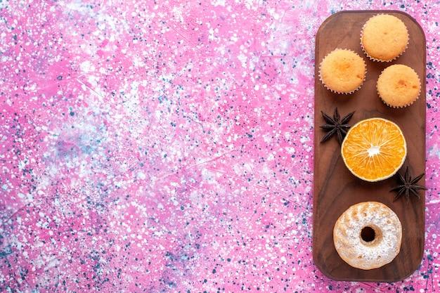 Vista dall'alto di piccole torte con fetta d'arancia sulla superficie rosa Foto Gratuite