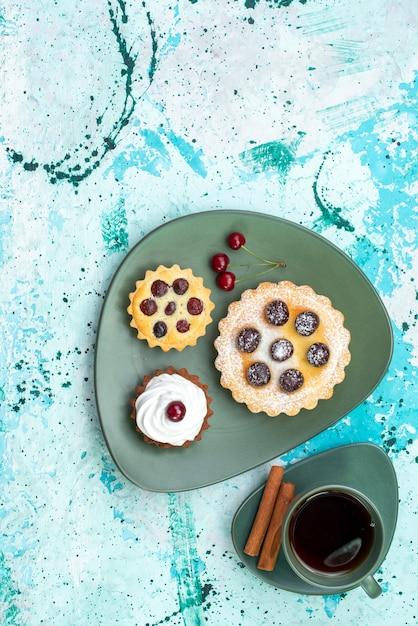 Вид сверху маленькие пирожные с чаем и корицей на голубом столовом пироге с вишневым фруктовым сладким Бесплатные Фотографии