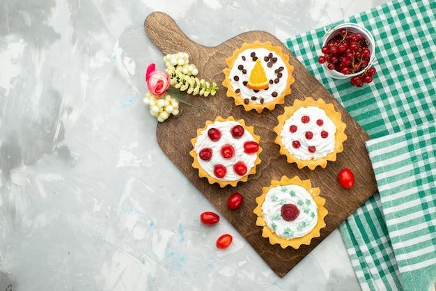 トップビューライトグレーデスク砂糖甘いの新鮮な果物と小さなクリームケーキ 無料写真