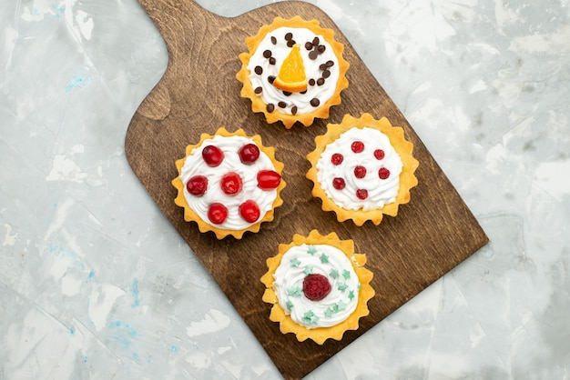 Vista dall'alto piccole torte alla crema con frutta sulla superficie grigio chiaro zucchero dolce Foto Gratuite