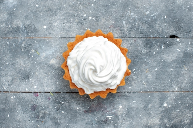 Vista dall'alto piccola torta cremosa al forno deliziosa isolata sulla foto di sfondo grigio biscotto dolce zucchero Foto Gratuite