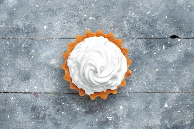 上面図灰色の背景のケーキビスケット甘い砂糖の写真に分離されたおいしい焼きたての小さなクリーミーなケーキ 無料写真