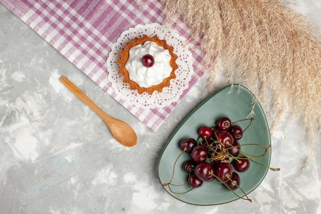 トップビューライトテーブルケーキティーフルーツスイートクリームに新鮮なチェリーと小さなクリーミーなケーキ 無料写真