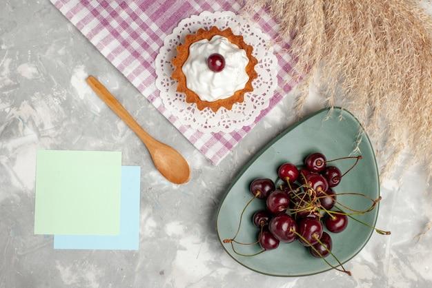 トップビュー明るい背景に新鮮なサワーチェリーと小さなクリーミーなケーキフルーツケーキ甘い焼きクリーム 無料写真