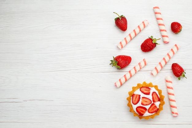 Вид сверху маленький сливочный торт со свежей клубникой и конфетами на светлом фоне торт сладкое фото фруктово-ягодная выпечка Бесплатные Фотографии