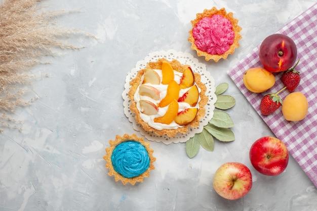 トップビュースライスしたフルーツと白いクリームとクリーミーなケーキとライトホワイトのデスク上のフルーツと小さなクリーミーなケーキフルーツケーキビスケットクッキー甘い 無料写真