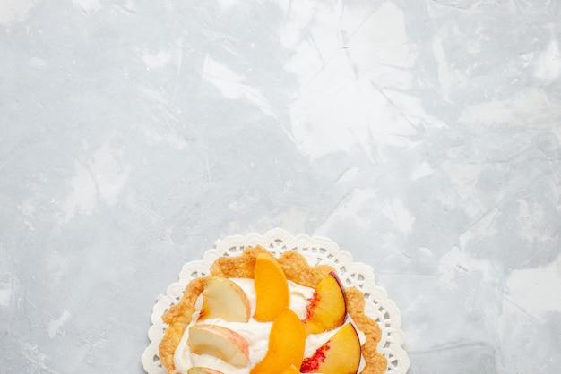 Vista dall'alto piccola torta cremosa con frutta a fette su di essa sulla scrivania a luce bianca torta di frutta gusto biscotto dolce biscotto Foto Gratuite