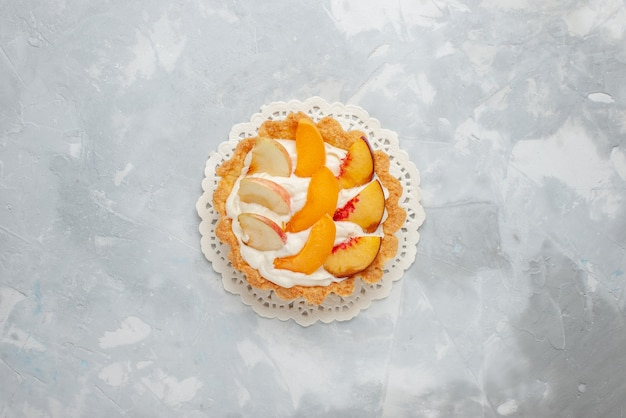明るい背景のフルーツケーキ甘いビスケットクッキーにスライスされたフルーツとその上に小さなクリーミーなケーキの上面図 無料写真