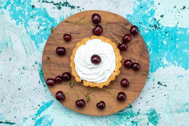 上面図水色の背景のケーキ甘いビスケットクリームにサワーチェリーと小さなクリーミーなケーキ 無料写真