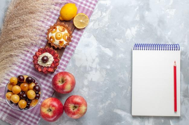 Vista dall'alto piccole torte cremose con mele rosse fresche ciliegie e limone sulla scrivania bianca torta di frutta biscotto crema dolce Foto Gratuite