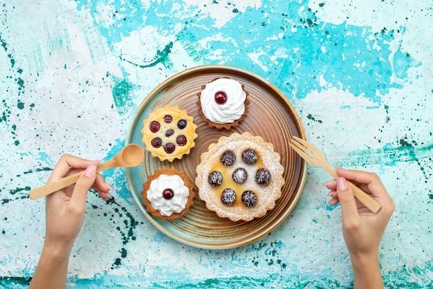 Vista dall'alto piccole torte cremose con frutta zucchero in polvere sullo sfondo azzurro torta crema cuocere dolce Foto Gratuite