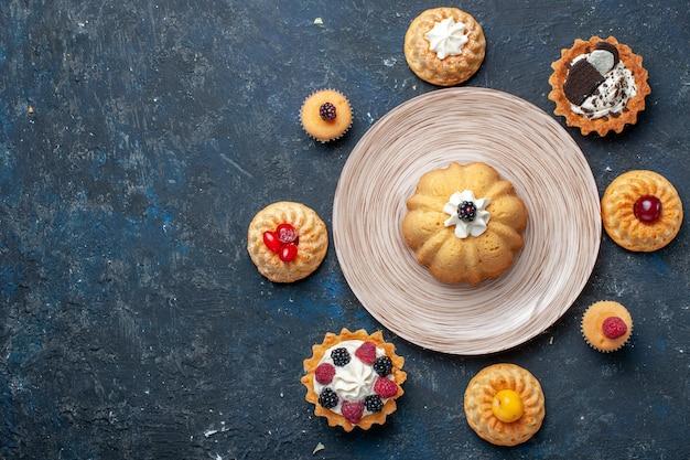 暗い机の上に形成された異なる小さなおいしいケーキの上面図ビスケットケーキ甘いフルーツ焼き 無料写真