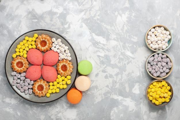 トップビュー白い机の上のクッキーとキャンディーと小さなおいしいケーキキャンディー甘いビスケットケーキパイシュガーパイクッキー 無料写真