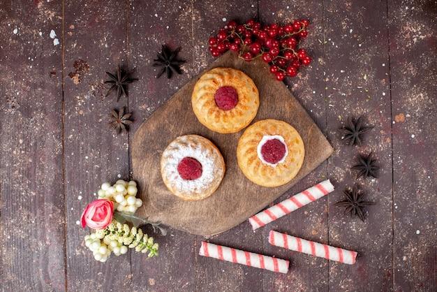 茶色の木製デスクケーキの甘い果物の写真にスティックキャンディーと一緒にラズベリーと新鮮なクランベリーの小さなおいしいケーキの上面図 無料写真