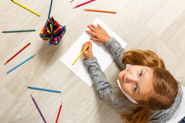 Top view of little girl painting, looking at camera and sitting on the floor. Premium Photo