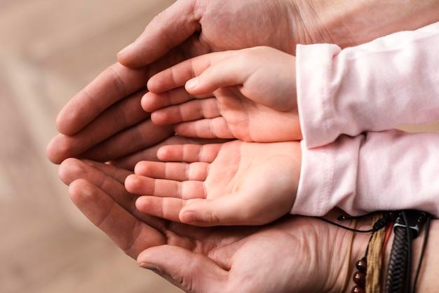 Vista dall'alto della bambina che mette le mani nelle mani del padre Foto Gratuite