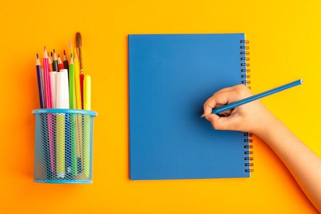 オレンジ色の表面のコピーブックに何かを描いたり書いたりする小さな子供を上面図 無料写真
