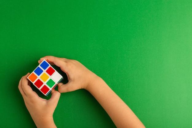 녹색 표면에 루빅스 큐브를 가지고 노는 상위 뷰 작은 아이 무료 사진