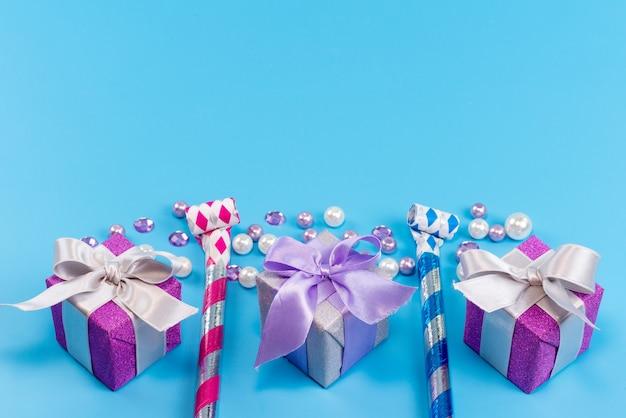 Una vista dall'alto piccole scatole viola per il compleanno isolato sul blu, festa di compleanno Foto Gratuite