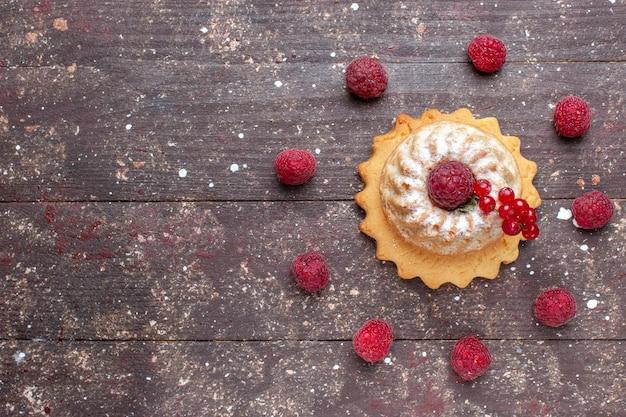 Вид сверху маленький простой торт с сахарной пудрой малины и клюквы на коричневом фоне ягодный фруктовый торт сладкая выпечка Бесплатные Фотографии
