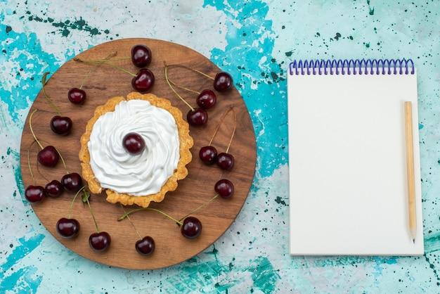 上面図ブルーライトテーブルケーキのクリームとフルーツの小さなおいしいケーキ甘いクリーム焼きフルーツティー 無料写真