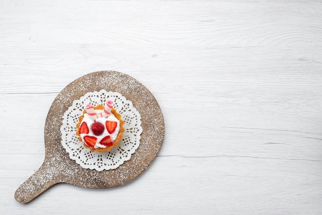 上面図白い背景のケーキベリー甘い砂糖焼きにクリームとスライスしたイチゴと小さなおいしいケーキ 無料写真