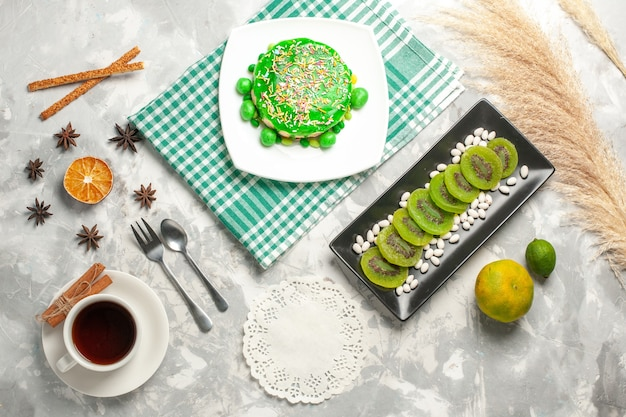 Top view little yummy cake with kiwis and cup of tea on white surface sugar bisciut sweet cake bake cream cookie Free Photo