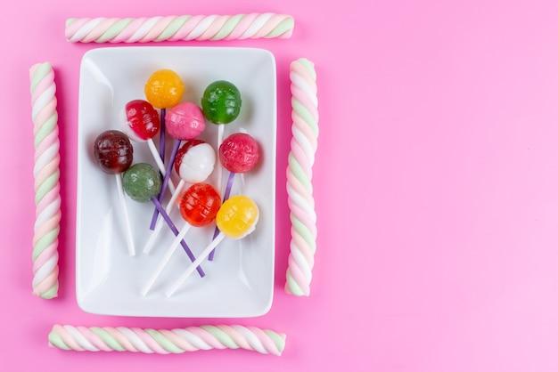 Una vista dall'alto lecca-lecca e marshmallow dolci e appiccicosi su dolciumi di colore rosa e zucchero Foto Gratuite