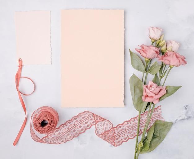 結婚式の招待状と花のトップビュー素敵なアレンジメント Premium写真