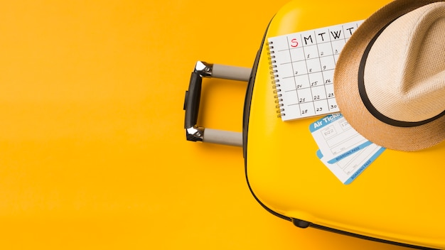 Top view of luggage with hat and calendar and copy space Free Photo